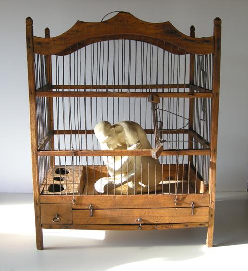 L'homme en cage (Ht 41 X 32 X 22 cm Céramique et cage bois métal)